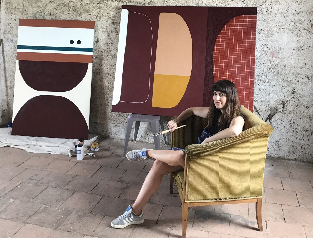 Portrait of Rachael McCully the australian artist in her studio next to large scale abstract canvasses