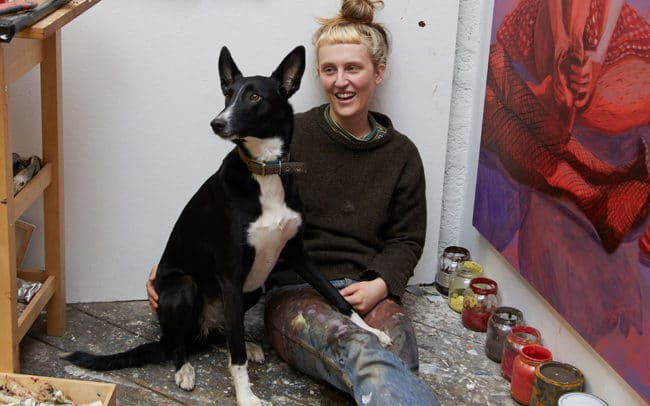 Portrait of artist and painter Nettle Grellier in her Stroud studio with dog